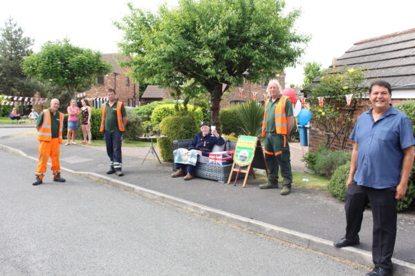 This image shows a street with 3 men in high-vis jackets, and a man in a blue shirt stood smiling. There is an elderly man sat in a chair in between them, raising a glass in celebration and smiling.