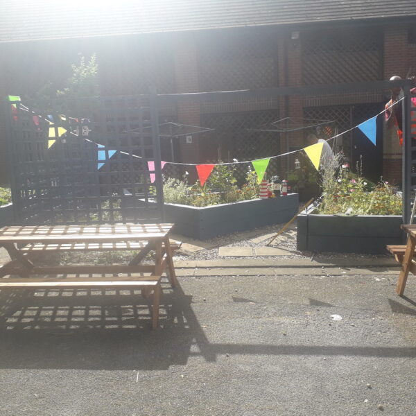This picture shows the sun shining down onto an empty picnic bench with multi coloured bunting handing across the image