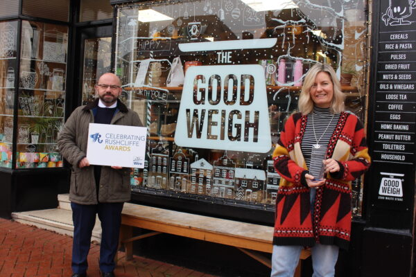 Nigel Carter from Streetwise presents Kate Cox at The Good Weigh with her environment award copy. The image shows a man and a woman stood in front of a shop window with the signage 'Good Weigh'. The man is stood to the left and is holding a Rushcliffe Award sign and the woman stands to the right, holding an award and smiling.