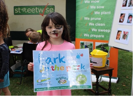 A little girl with her face painted to look like a dog, smiles and holds a sign that says 'Lark in the park'