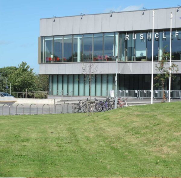 A large grey building with large windows and 'Rushcliffe' written across the windows in white. There is grass all around and bicycles secured to a fence at the front of the building.