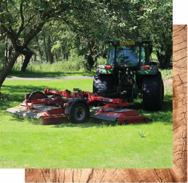 A tractor is pictured in a grassy area with a tree overhanging it. The tractor is sat behind a deconstructed red piece of machinery that is sat on the grass.