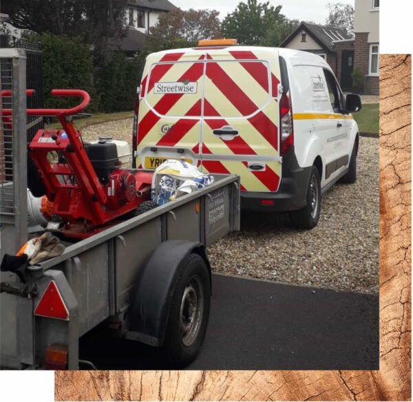 A Streetwise Environmental van with yellow and red stripes on the back doors is shown connected to a small trailer which contains a stump grinder for the safe removal of tree stumps..