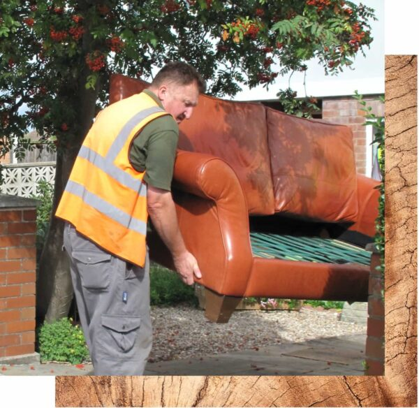 A man in an orange hi-vis jacket is lifting a large brown leather sofa that is missing it's cushions. There is a large tree in the background and a red brick wall behind the man