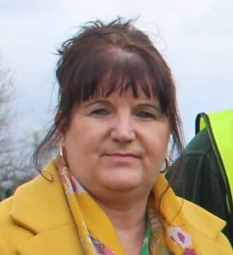 Susan Harvey, Business Development Manager. The picture shows a lady with dark hair tied up, wearing a yellow coat with a flowery yellow scarf.