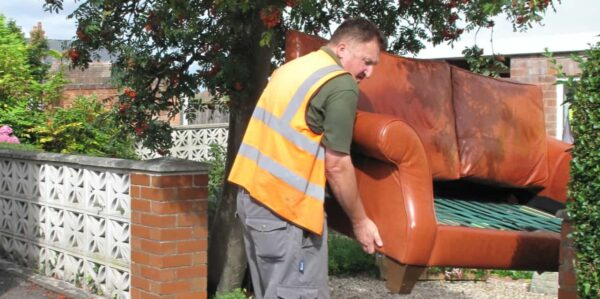 A Streetwise bulky collection operative in an orange hi-vis jacket is lifting a large unwanted brown leather sofa. There is a large tree in the background and a red brick wall behind the man.