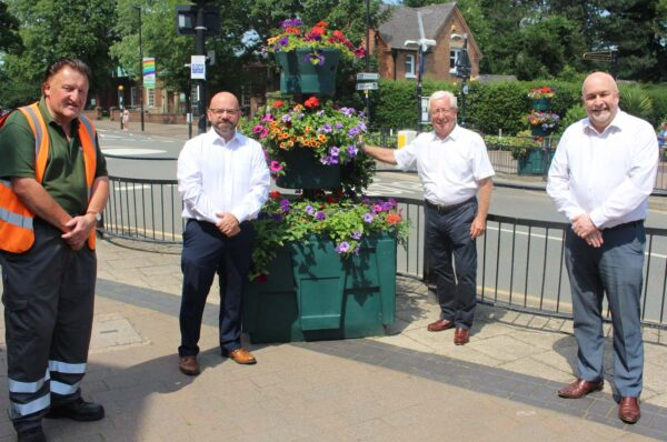 Streetwise employee Chris, Managing Director Nigel Carter, Cllr Gordon Moore, and chairman Dave Mitchell are pictured on Central Avenue stood next to large baskets full of colourful flowers.