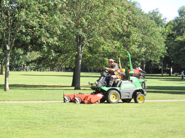 The image shows a grassy field with trees in the background. In the foreground, a man is driving a ride on lawn mower across the grass.