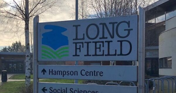 The image shows a close up of a sign that says 'Long Field'.