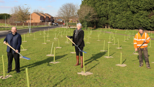 Streetwise Managing Director, Nigel Carter, Cllr Abby Brennan, and Streetwise operative Bernard Sampson, stand with shovels in the middle of a grassy area fully of newly planted trees