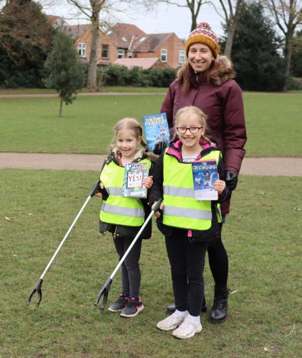 Two little girls in high-vis jackets holding litter pickers stand in front of their mother, they are holding children's books by Tom Fletcher, Michael Morpurgo and Tom Gates, and smiling.