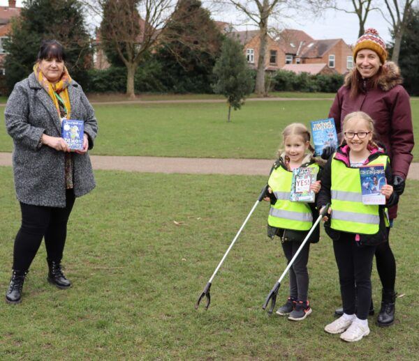 Two little girls in high-vis jackets holding litter pickers stand in front of their mother, they are holding children's books by Tom Fletcher, Michael Morpurgo and Tom Gates, and smiling. A dark haired lady in a grey coat stands across from them smiling and holding a book.
